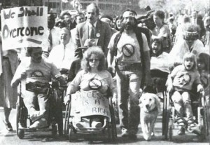 """a black and white picture shows a crowd of people, some of whom use wheelchairs, one man has a service dog with him. They are children and adults and appear to be chanting or singing. One person holds a sign that says, """"We shall overcome."""""""