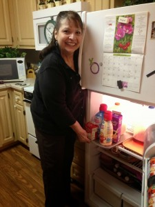 Bobbette standing in front of refridgerator pulling out a tray of creamers from the top shelf