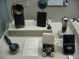 several early hearing aids that look like microphones and small radios that people had to hold or wear around their neck
