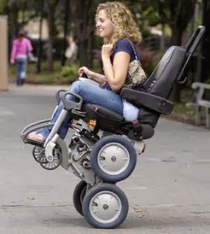 Woman on a wheelchair on 2 wheels outdoors