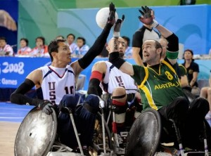 Picture of 3 men in wheelchairs fighting for control of the rugby ball all with their hands up in the air. Shirts say US and Australia.
