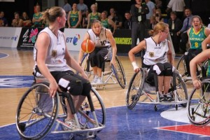 on the basketball court, shows 4 women going for the ball in wheelchairs