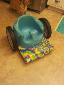baby Bumbo seat with wheels and tie-dyed foot platform