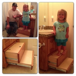 Child standing on top of two sliding drawer stairs built bathroom sink cabinet.