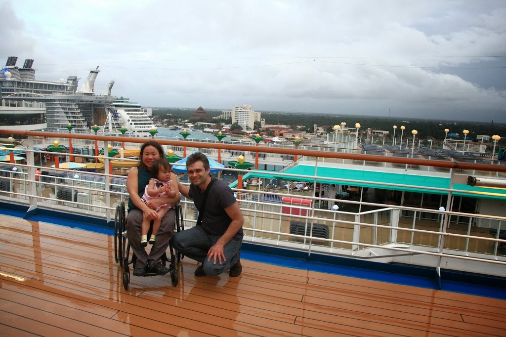picture of shannon in her manual wheelchair and her daughter on her lap and her husband next to them with a view of the ship and the city skyline in the background