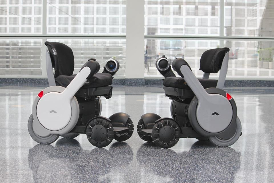 picture of 2 whill wheelchairs that are white grey and black and smaller than typical wheelchairs. They have different hand rests that come down and up