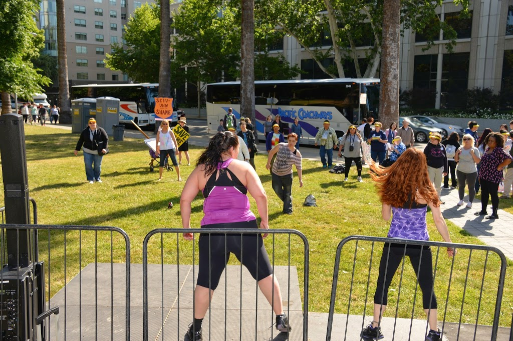 two women lead a group of people in an outdoor exercise routine.