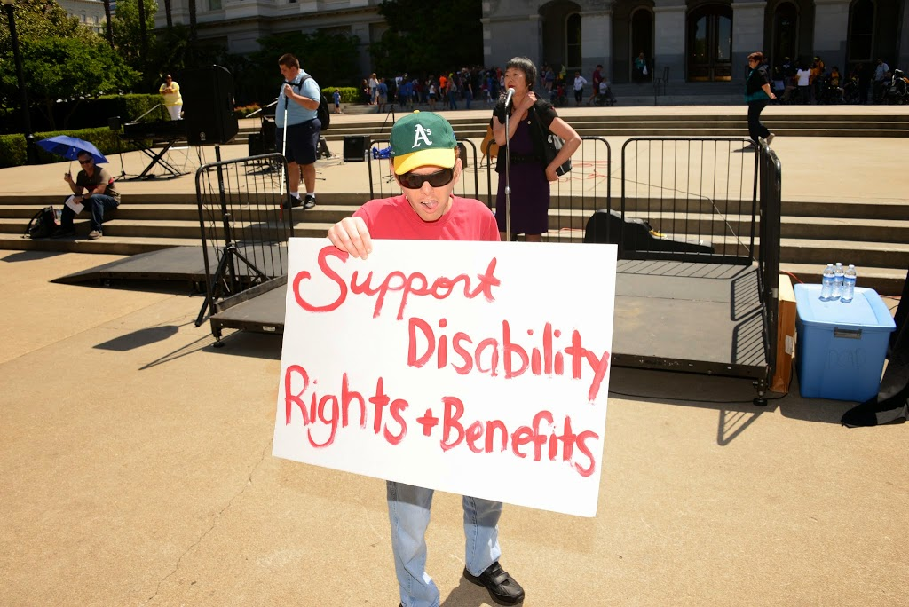 "a man in front of the stage with a speaker holds a sign that reads, ""Support Disability Rights & Benefits."""