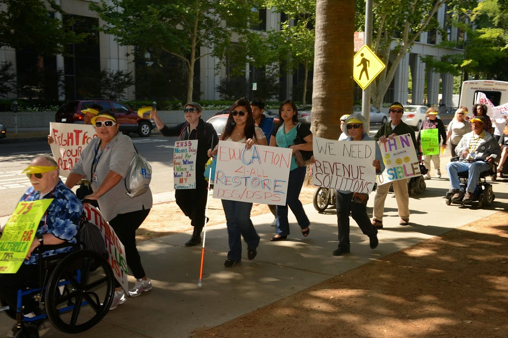 """a woman holds a sign that reads, """"the time is now for equality,"""" in front of the CA State Capitol. a lot of marching people behind her with different apparant disabilities"""