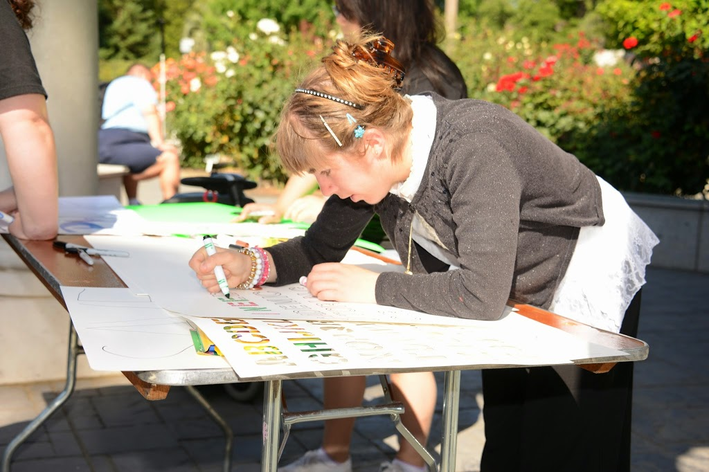 a woman draws on a poster that she is creating for the DCAD Rally and March.