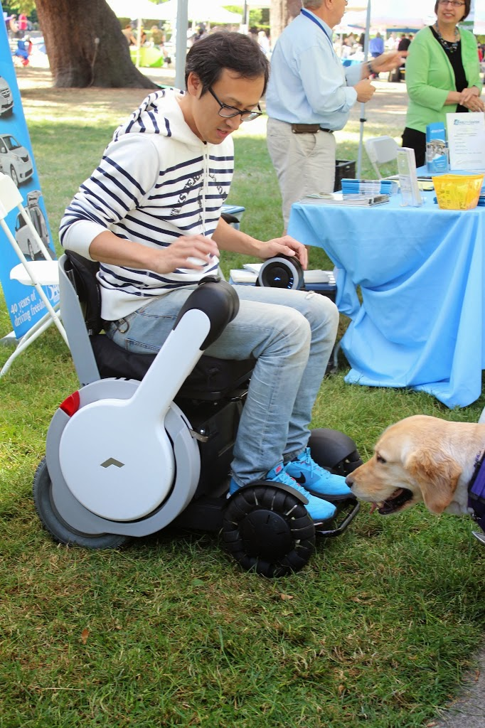 a man sits in a Whill personal mobility device, which he is able to use on the grass.