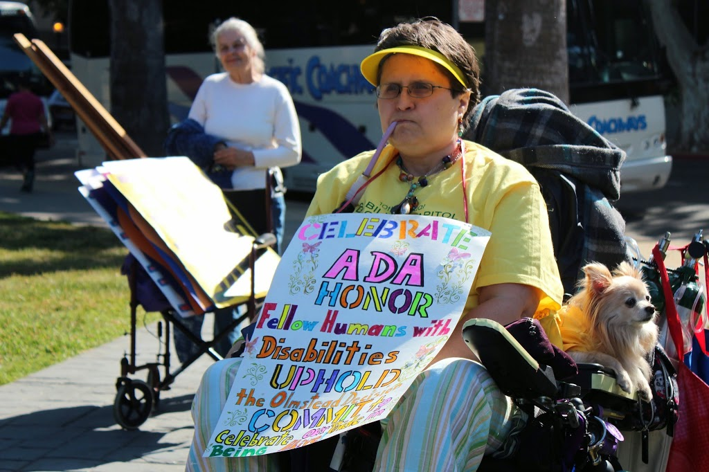 "a woman using a wheelchair holds a sign that reads, ""celebrate ADA honor fellow humans with disabilities uphold the olmstead decision commit to celebrate our pride in being alive!"" her small dog is also seated in the wheelchair."