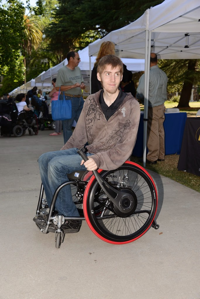 a man using a wheelchair holds a wijit device attached to his spoke, which allows him to control his chair easier with less shoulder mobility.