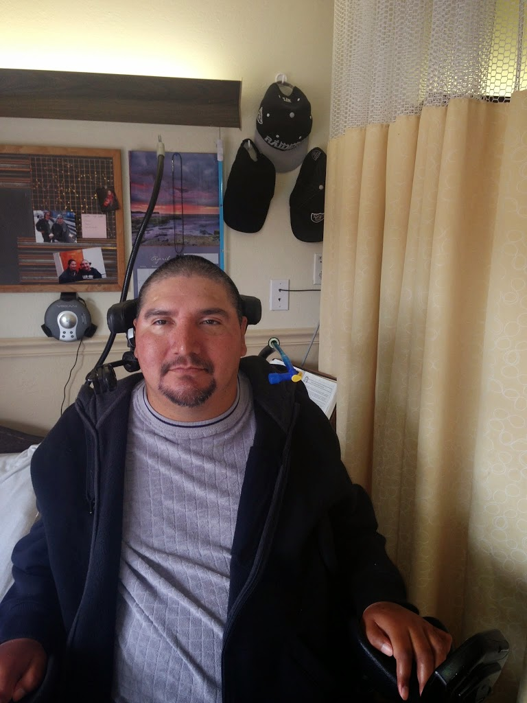 picture of Juan jose in a wheelchair in his room with his camelbak tubing showing and some hats in the background
