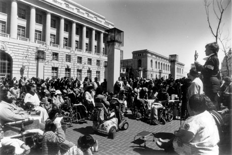 Black and white photo of a bunch of people including many that use wheelchairs listening to a woman speak outside government building