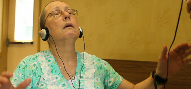 women with glasses and eyes closed looking like she is praying and has on headphones