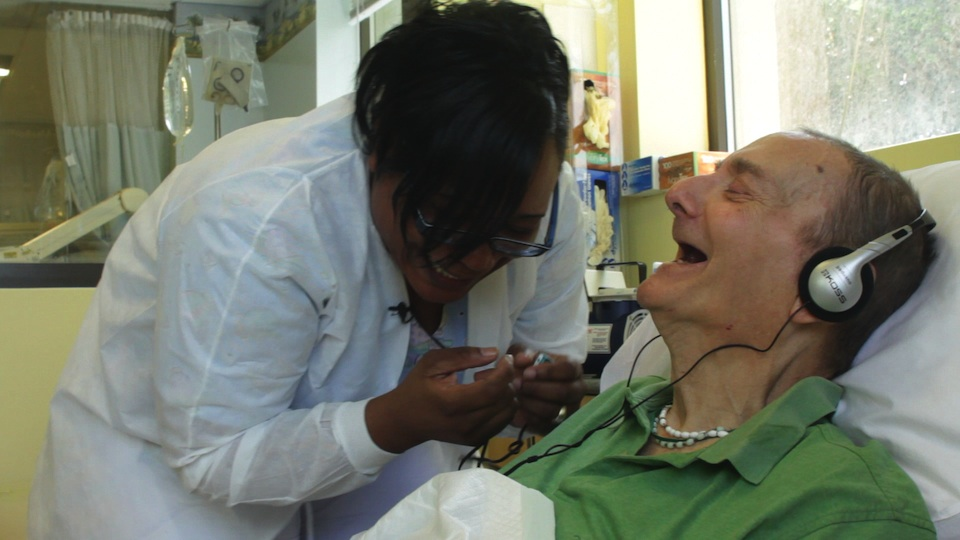a nurse bending over an elderly patient in a hospital bed that is listend to headphones