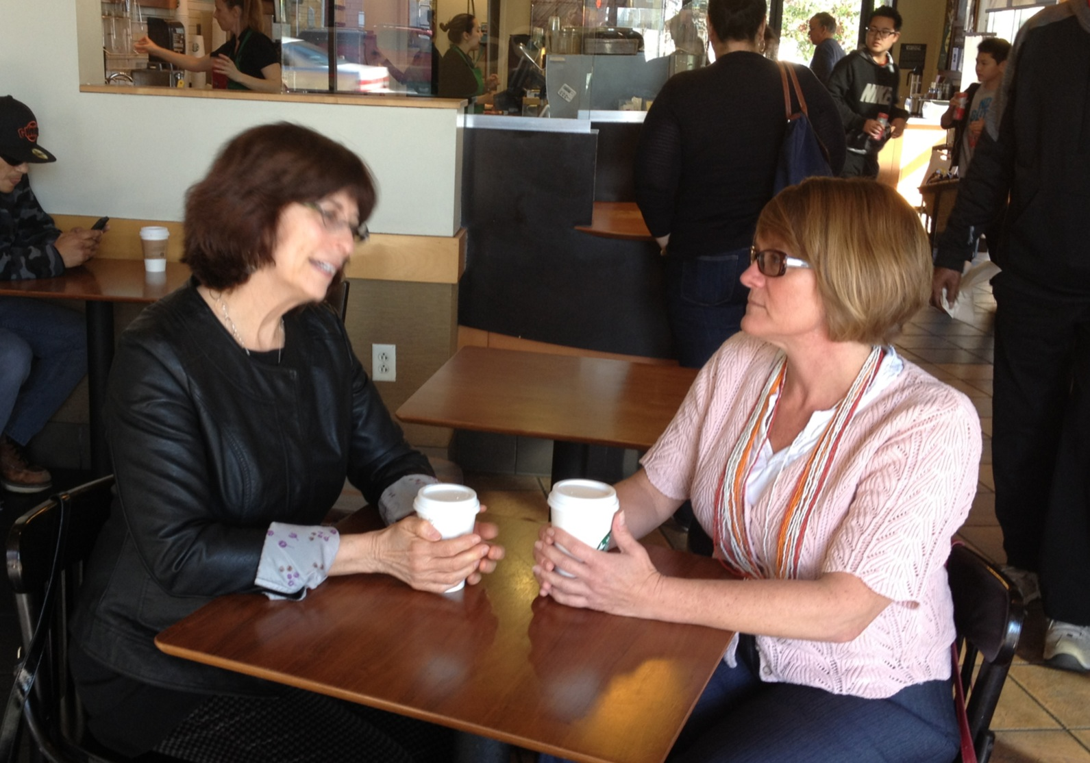 two women sitting at a coffee shop at a table talking and drinking coffee
