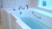 picture of an accessible tub with a walk in door and blue water inside the white tub with silver metal handles