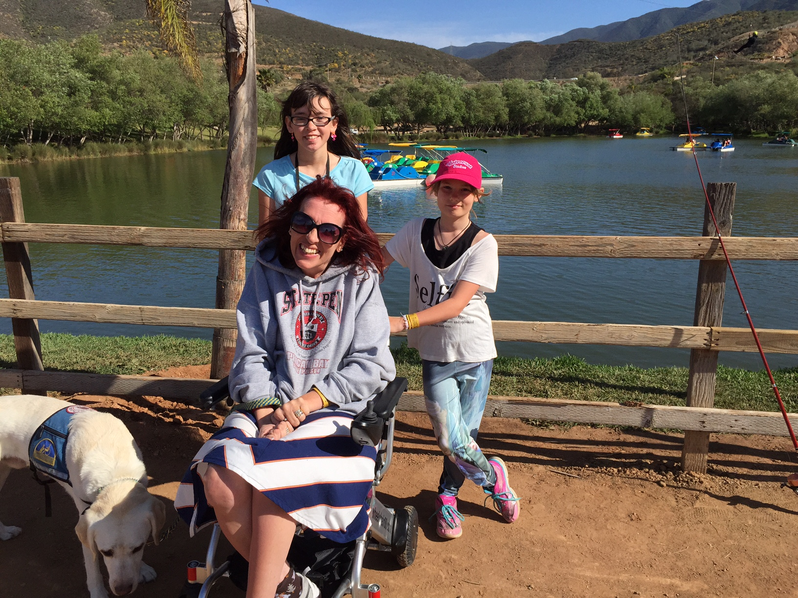 Picture of Aleta with her two daughters she is sitting in a wheelchair smiling and her two daughters are behind her standing and there is a lake behind them