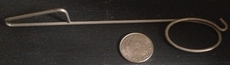 picture of the metal device next to a quarter it is thin and metal and about the length of 5 quarters
