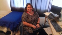 Picture of Nicole seated and smiling at her computer desk and using a Braille note.