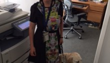 picture of Amy Liu in her office standing with her guide dog Donna.