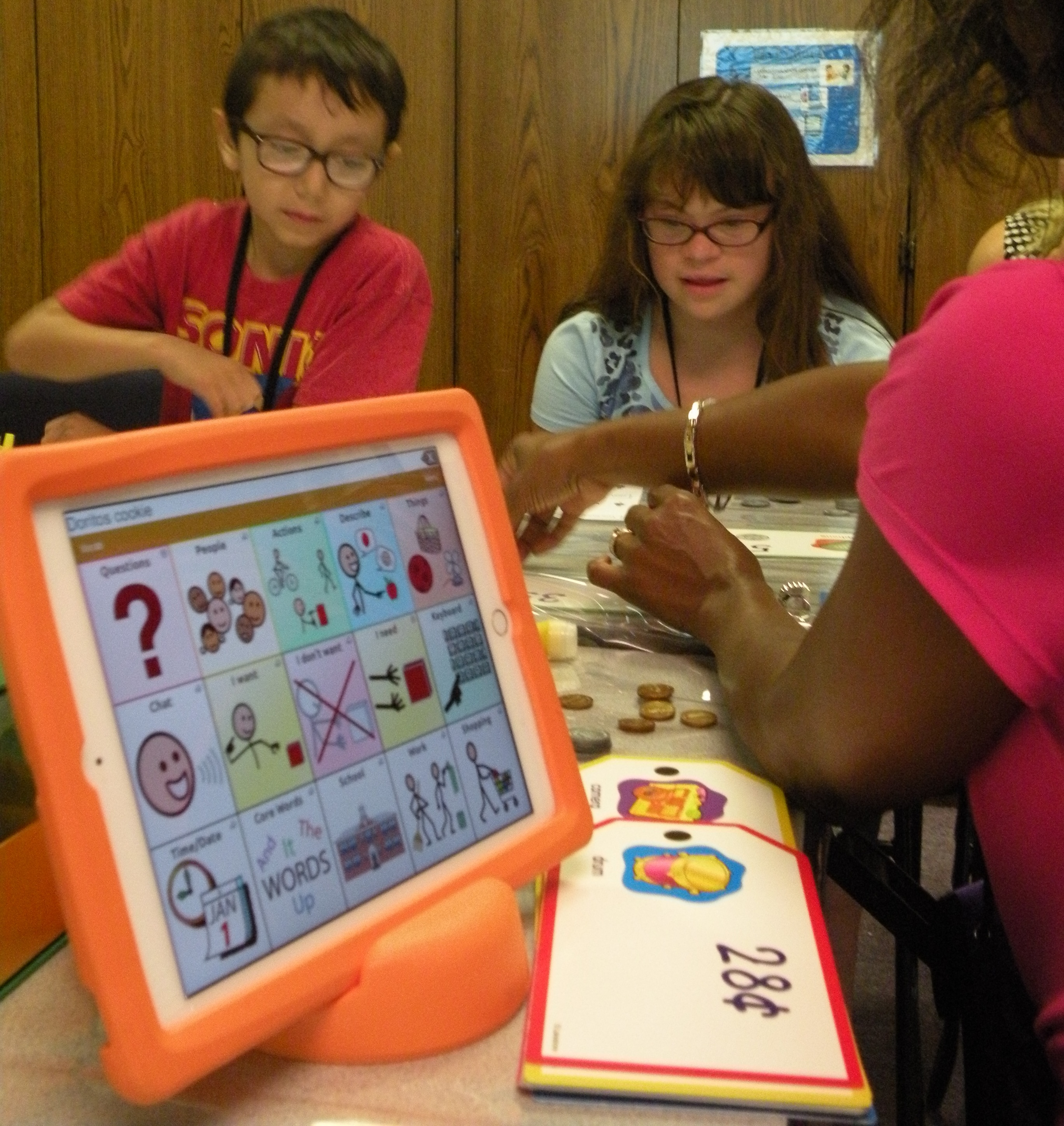 An orange tablet sized AAC device with different stick figures on it and two children and a teacher sitting at a desk
