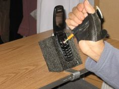 cell phone on a table with a stand and a foam background, user using pencil to punch in numbers