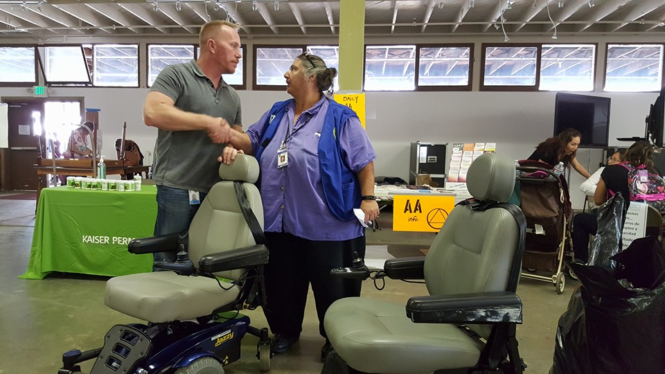 Clint Vigen from the CA Dept. of Rehabilitation and Teresa Favuzzi, Exective Director of CFILC shake hands over the power chairs they helped to get to the victims of the fire