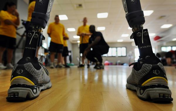 close up of robotic prostetic legs and people in the background looking at them in yellow shirts