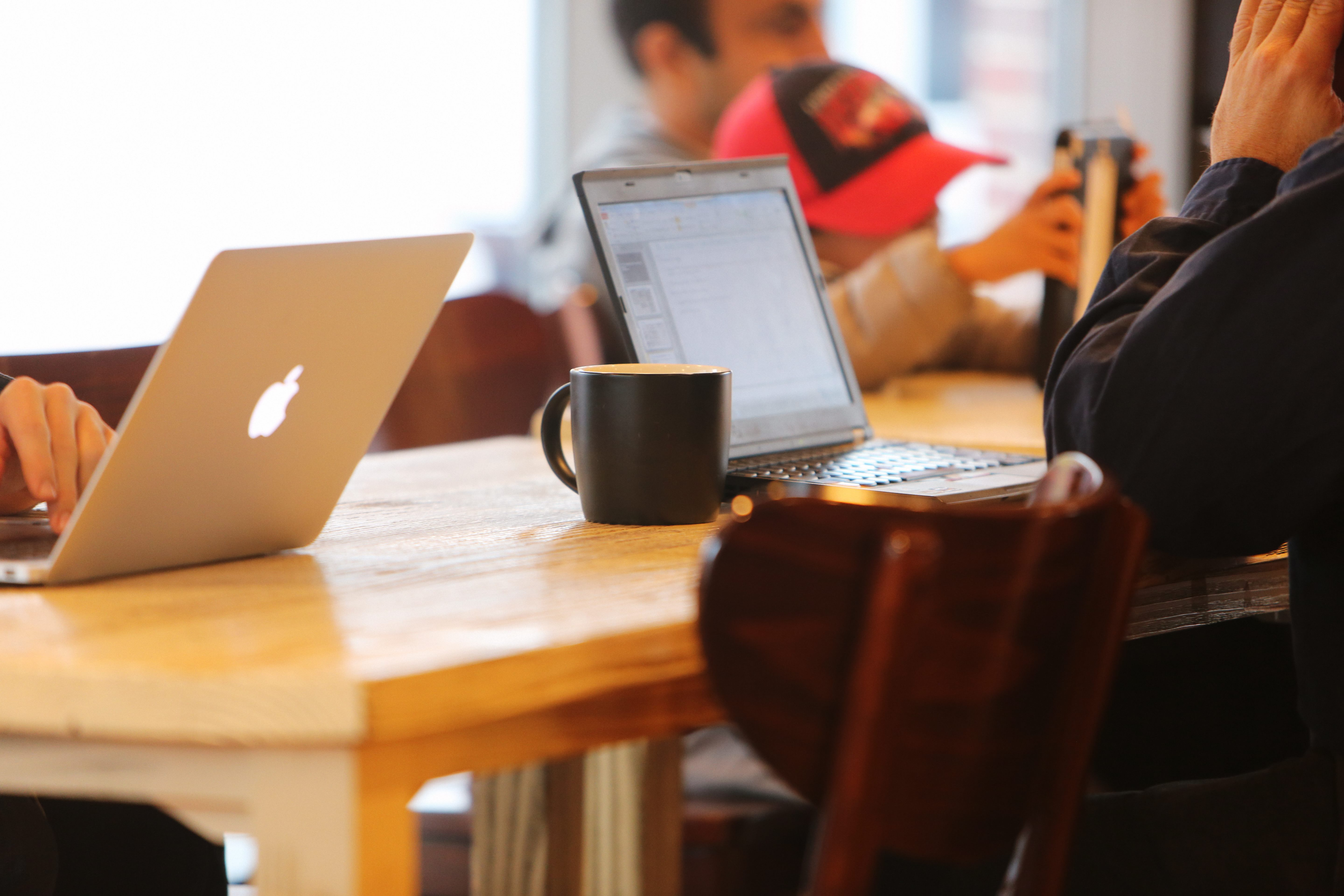 Picture of 2 laptops at a table with a cup of coffee on it and a boy in the background faded out