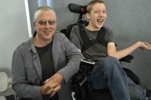 picture of garry (blogger) with his son who uses a wheelchair.  Both are smiling and garry is kneeling down.