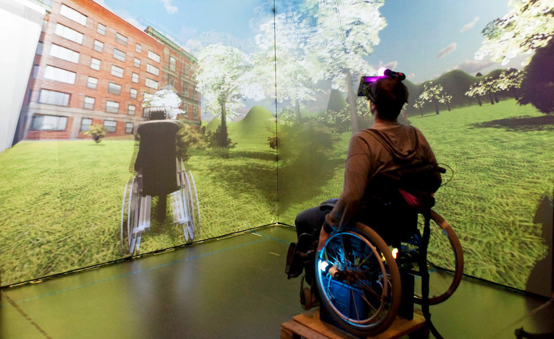 a person in a wheelchair wearing VR goggles and a scene of a meadow and buidling on the wall