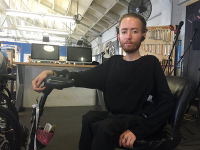picture of beareded younger man in a scooter wearing headphones and looking at camara