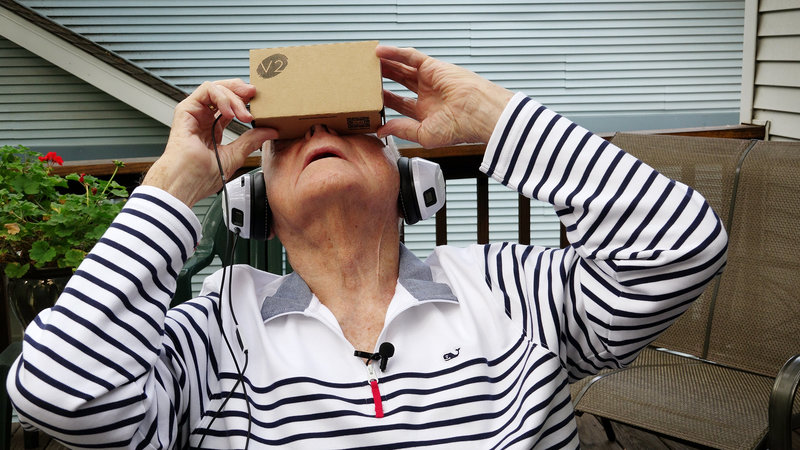 an older woman in striped shirt wearing headphones and looking through cardboard virtual reality box