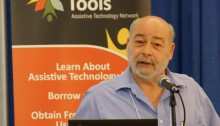 gnetleman in front of a podium is talking in front of an Ability Tools banner