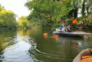 picture of young man padddling in kayak with adaptive paddle in back of kayak
