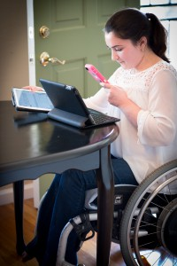 picture of woman using two tablets and smart phone and wheelchair at table