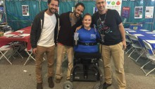 kim lathrop and her TOM cohort. She is wearing a blue shirt and uses a wheelchair and three other gentleman are smiling and standing with their arms around her.