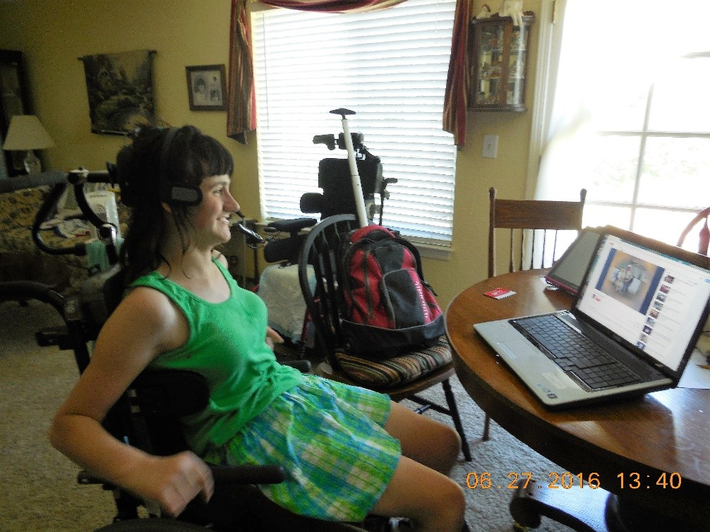 catherine stiting at a dining room table in her wheelchair and in front of computer using the mouse heaadset