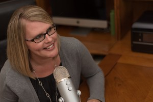 Picture of blonde women in glasses smiling while speaking into a microphone