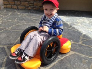 Picture of little boy in red hat sitting on the orange firefly scoot outside