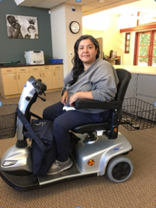 Photo of Ms. Gomez sitting and smiling in her new scooter