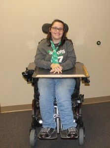 Photo of young women sitting in a power chair smiling