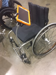 Manual chair with long arm attached to a mounting system holding an Ipad with orange case.