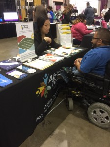 Women sitting behind a table speaking with a young man in a power chair