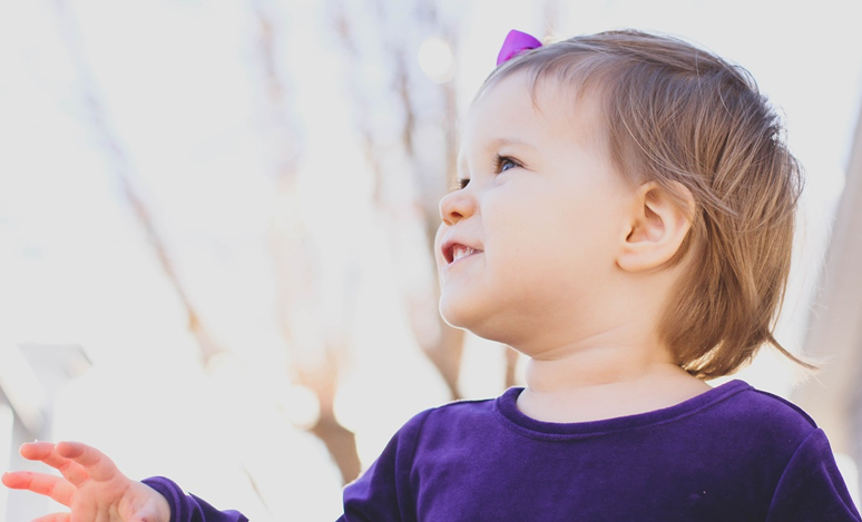 Picture of smiling toddler wearing a purple shirt and bow in hair
