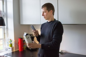 Man standing in kitchen holding his phone up to a milk carton