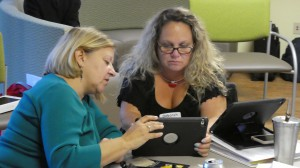 Two women sitting with an ipad,  one women is showing the other how to access a speech app.